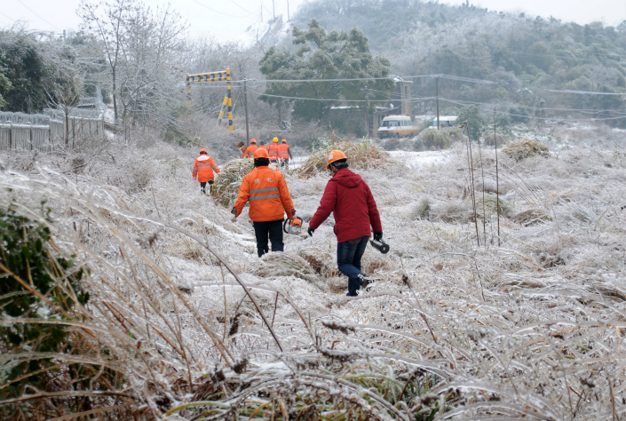 Workers in China's southern Jiangxi province make their way to the fault location of a power line covered by snow and ice on Sunday. Photo: VCG