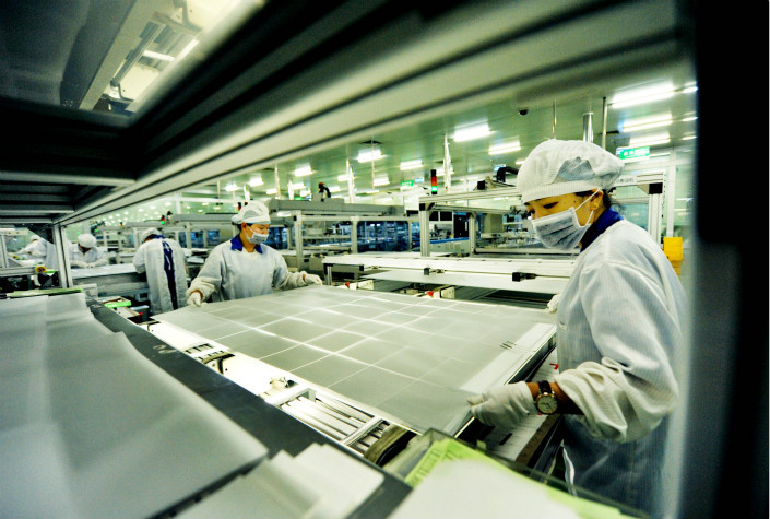 "Workers at a JinkoSolar factory in China's Jiangxi province assemble solar panels for export to South Africa in 2015. The company announced that its board of directors had authorized the company to make final plans for ""an advanced solar manufacturing facility in the U.S."" Photo: IC"