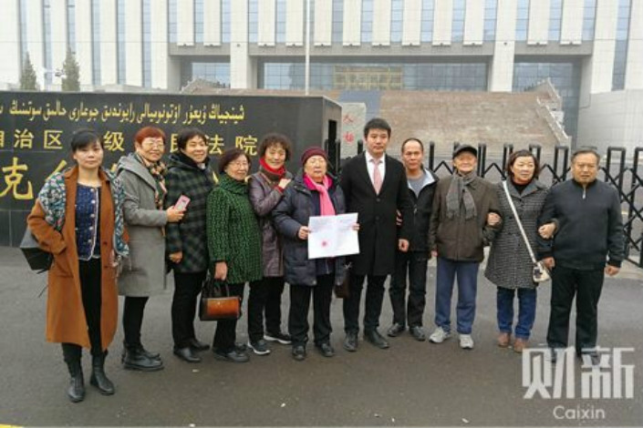 Zhou Yuan, fourth from the right, poses with relatives and his lawyer outside of the Xinjiang Uygur Autonomous Region High People's Court shortly after he was exonerated on Nov. 30. Zhou has said the officials responsible for the miscarriage of justice should be held accountable. Photo: Wang Heyan/Caixin