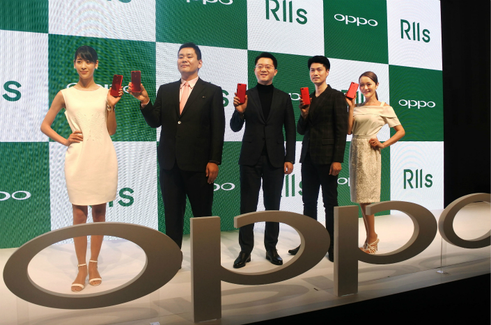 Deng Yuchen (center), head of the Japanese arm of Chinese smartphone maker Oppo Electronics Corp., poses for photos during a news conference in Tokyo on Wednesday, during which the company announced its plans to start selling Oppo handsets in Japan. Photo: VCG