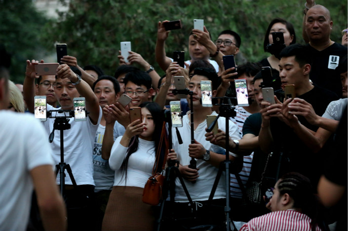 People use their mobile phones to film a performance in Zhengzhou, Henan province in September. Smartphone shipments in China declined 4.9% for the whole of 2017, according to market research firm IDC. Photo: VCG