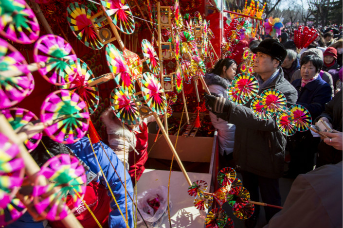 People buy traditional handmade pinwheels at Changdian Temple Fair in Beijing during last year's Lunar New Year holiday. The annual fair, which dates back to the Ming dynasty which ruled from 1368 to 1644, was stopped during World War II and was revived after a long hiatus in 2001, but many people have long complained that its now become commercialized. Photo: VCG