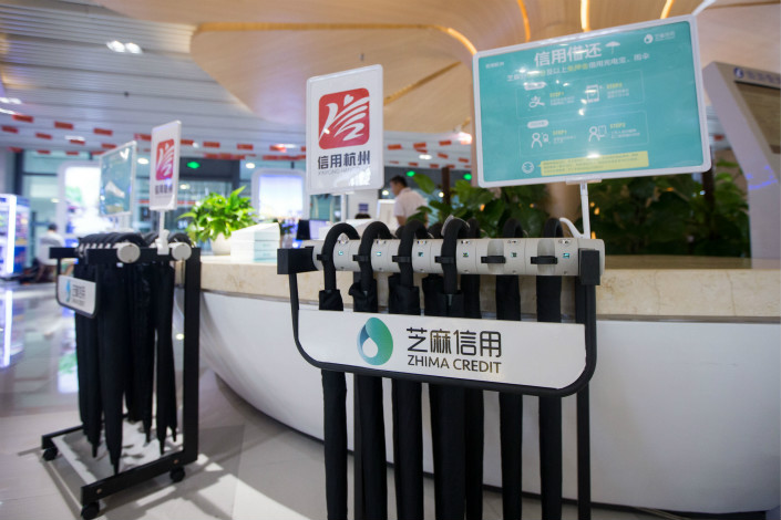 Above, a Zhima Credit umbrella-rental stand is seen in a shopping mall in Hangzhou, Zhejiang province. Zhima Credit has announced it will temporarily cease offering services to unlicensed banks, consumer finance companies, and online microlenders as of March. Photo: VCG