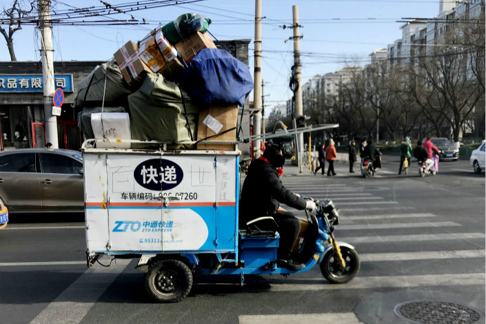 A courier delivers packages in Beijing on Jan. 29. Counterfeits were purchased from nine of 16 online shops targeted by the China Consumers Association in a recent test. Photo: VCG