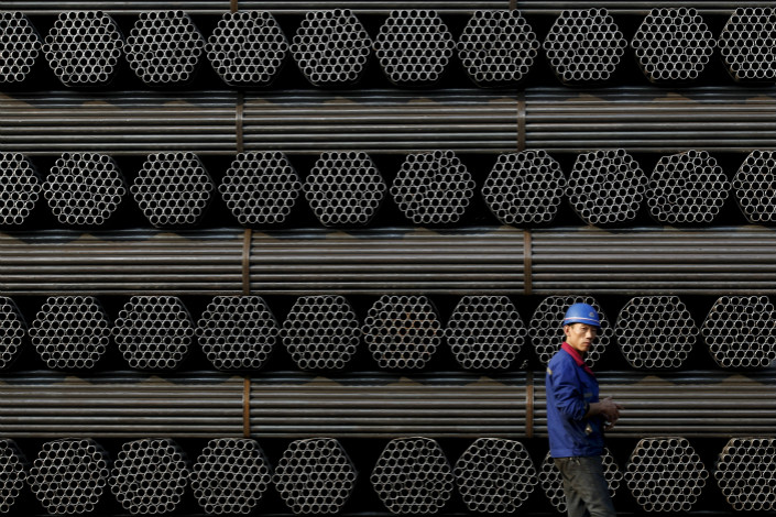A worker walks past steel pipe in Tangshan, Hebei province on Nov. 3. The city accounted for around 11% of the crude steel produced in China last year. Photo: VCG