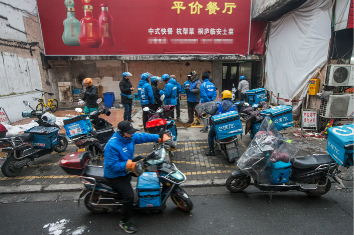 Ele.me deliverymen wait outside a restaurant on Jan. 31. Ele.me held 55.3% of the takeout market in the fourth quarter of 2017, followed by the food delivery division of Meituan Dianping, which had a market share of 41.3%. Photo: VCG