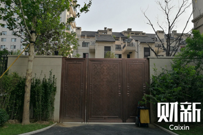 In September, a wooden gate separates the upscale homes of Xichen Yuanzhu from the affordable apartments for low-income families in neighboring Yupu Home Garden. Photo: Huang Ziyi/Caixin