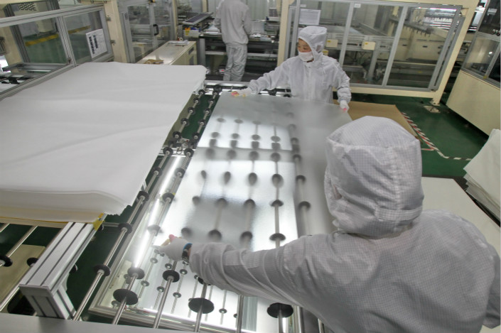 Workers in Nantong, Jiangsu province, assemble solar power modules. An analyst said the new standards primarily aim to control the addition of new solar power capacity and ensure the quality of solar products. Photo: VCG