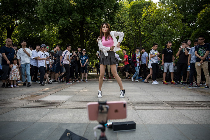 A webcasting hostess uses a smartphone to create a live webcast during the Douyu Festival on May 29 in Wuhan, Hubei province. Photo: VCG