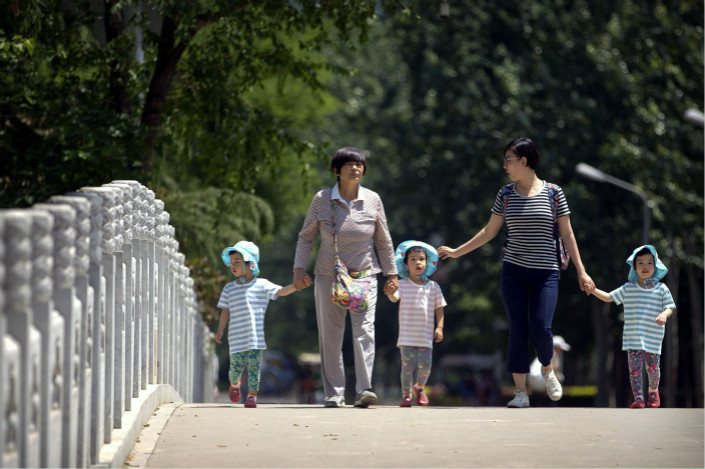 Women and children walk through a park in Beijing on June 1. Photo: IC