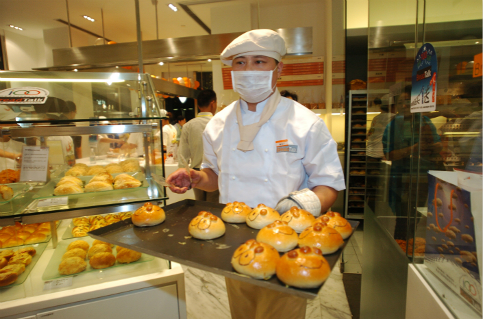 A baker sets out buns in a BreadTalk store in Shanghai in October 2016. Photo: IC