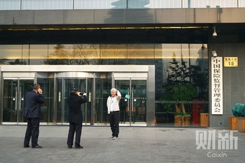 People pose for photos in front of the headquarters of China Insurance Regulatory Commission in Beijing. Photo: Caixin