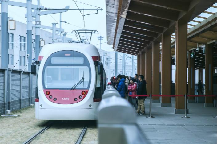 Passengers get on a train on Beijing's Xijiao Line. Photo: VCG