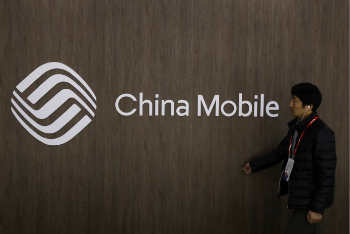 A man walks past the China Mobile logo at the Mobile World Congress in Barcelona, Spain, February 28, 2018. Photo: VCG