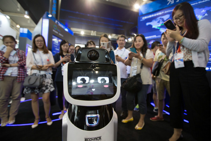 Visitors watch an Ecovacs robot on display at a trade fair in Nanjing, Jiangsu province in 2016. Photo: VCG