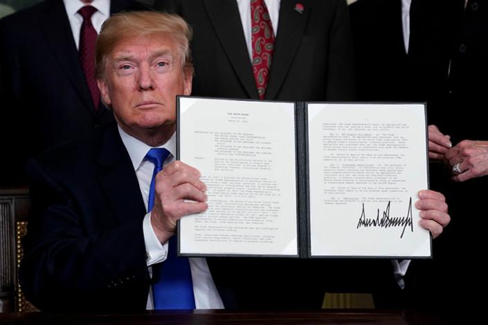 U.S. President Donald Trump holds up a signed executive memorandum targeting China on trade at the White House on Thursday. Photo: IC/UPI
