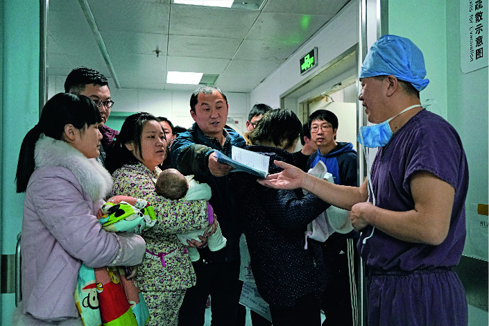 Li Long, a senior pediatrician at Children's Hospital of the Capital Institute of Pediatrics, a top pediatric facility in Beijing, is mobbed by a group of anxious parents seeking his advice as he emerges from an operating room on March 12.