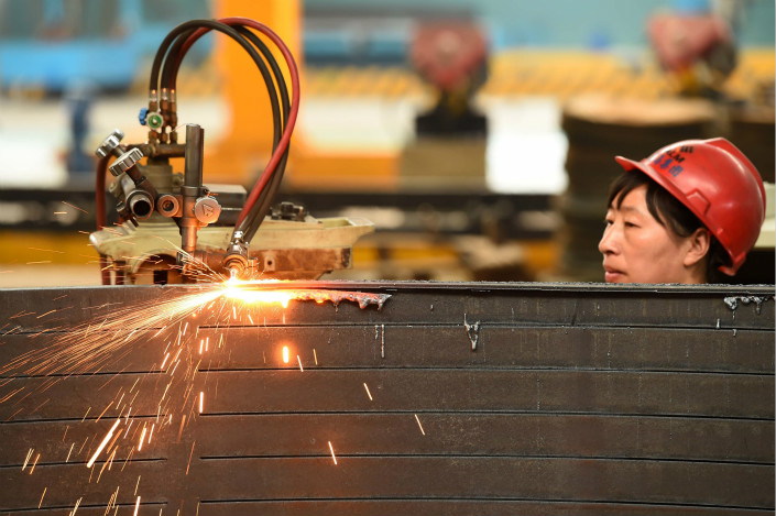 A worker welds wind power equipment on March 31 at a factory in Shandong province. Photo: VCG