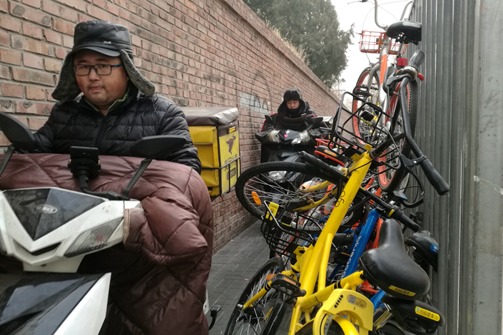 Deliverymen for Meituan's food takeout service ride past a heap of shared bikes from Mobike, Ofo and other companies in Beijing on Dec. 29. Photo: Wu Gang/Caixin