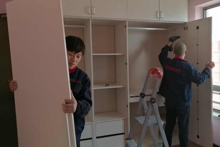 Moving-company workers disassemble a cabinet while moving furniture out of a home in Beijing on March 24. Photo: Wu Gang/Caixin