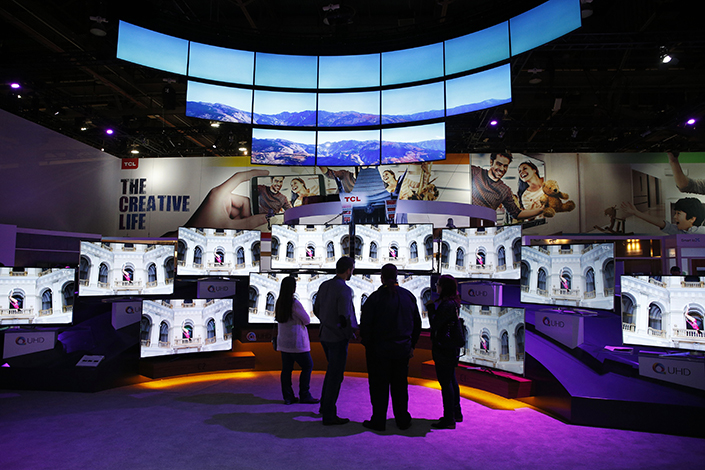 Visitors to the 2016 CES International electronics trade show in Las Vegas check out ultra-high definition TVs at the TCL booth. Photo: IC