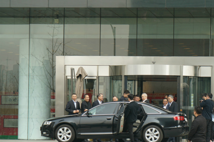 Vice Premier Liu He, third from right behind the car, leaves for a session of China's annual