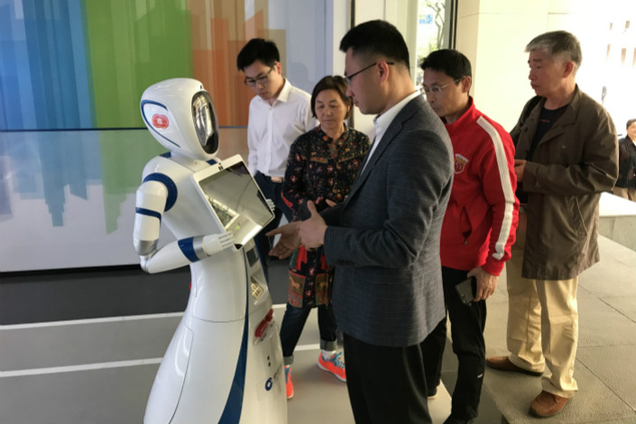 A visitor browses a tablet held by a robot teller at China Construction Bank's unmanned branch in Shanghai on Wednesday. Photo: Leng Cheng/Caixin