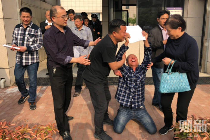 Zhou Zaichun, second from right, is overwhelmed with emotion on Wednesday after courts declared him and four other men not guilty of a 1996 murder for which they had already served years in prison. Photo: Xiao Hui/Caixin