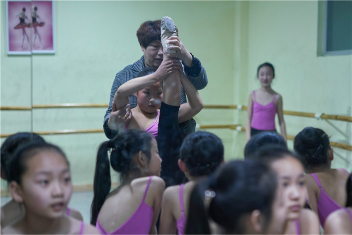Liu Qiuju helps her daughter Jiaojiao during a ballet class. Many mothers in the township have now become experienced coaches for their daughters, despite never having trained in ballet.