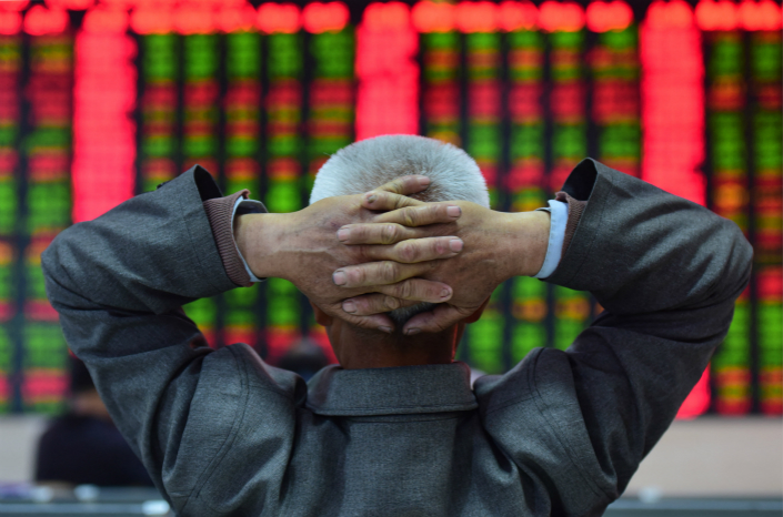 An investor watches the movement of share prices at a stock market trading hall in the eastern province on Anhui on April 13. Photo: VCG