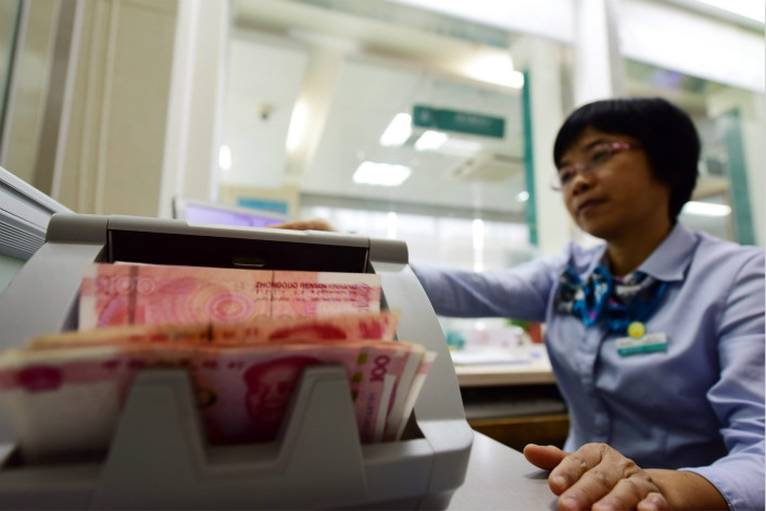 Bank staff count cash in Qionghai, Hainan province on April 18. Photo: IC