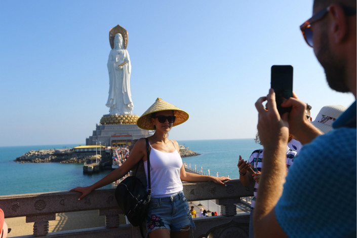Foreign tourists take photos in front of the Guanyin of Nanshan, a 354-foot-tall statue of the bodhisattva Guanyin, in Sanya, Hainan province on Feb. 17. Photo: VCG