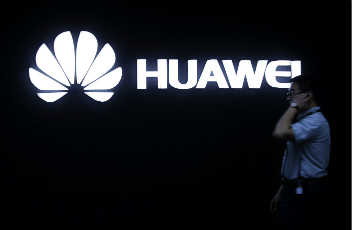 A man walks past a Huawei logo during a May 2016 launch event for the Huawei Matebook in Beijing. Photo: IC
