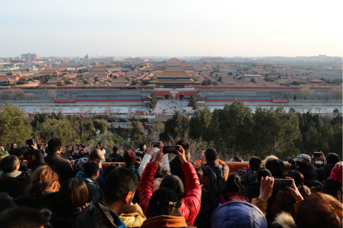 People use their smartphones to take pictures of Beijing's Palace Museum from the top of a hill in the capital's Jingshan Park on Feb. 20. Photo: VCG