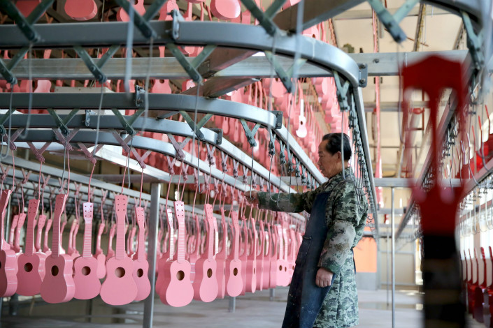 A worker inspects guitars at a factory in Shuyang county, Jiangsu province, on April 7. Photo: VCG