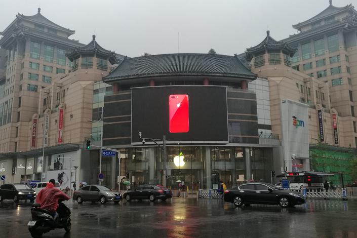An Apple store in Beijing's Wangfujing shopping district advertises the new red iPhone model on April 21. Photo: Wu Gang/ Caixin