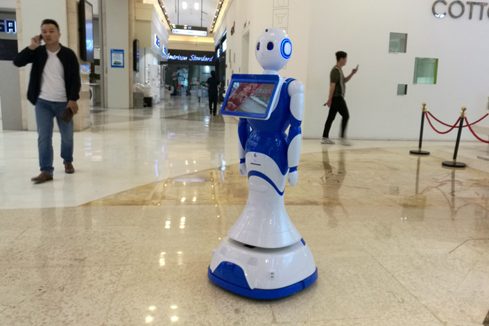 A guide robot that can respond to customer calls rolls around a furniture mall in Beijing on Saturday. Photo: Wu Gang/Caixin
