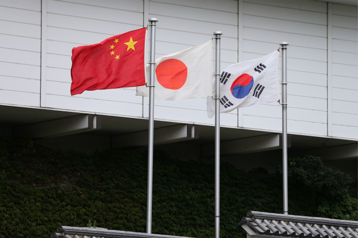 From left, the flags of China, Japan and South Korea are hoisted in Tokyo at the site of a meeting of trade ministers from the three countries in October 2016. Photo: VCG