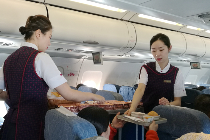 Flight attendants serve meals on an Air China flight from Beijing to Chengdu on April 22. Photo: Wu Gang/Caixin