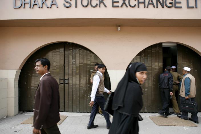People walk past a Dhaka Stock Exchange office in Dhaka, Bangladesh in 2011. Photo: IC
