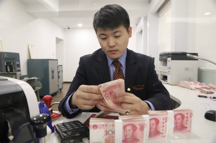 A bank employee counts money in Harbin, Heilongjiang province on March 29. Photo: VCG