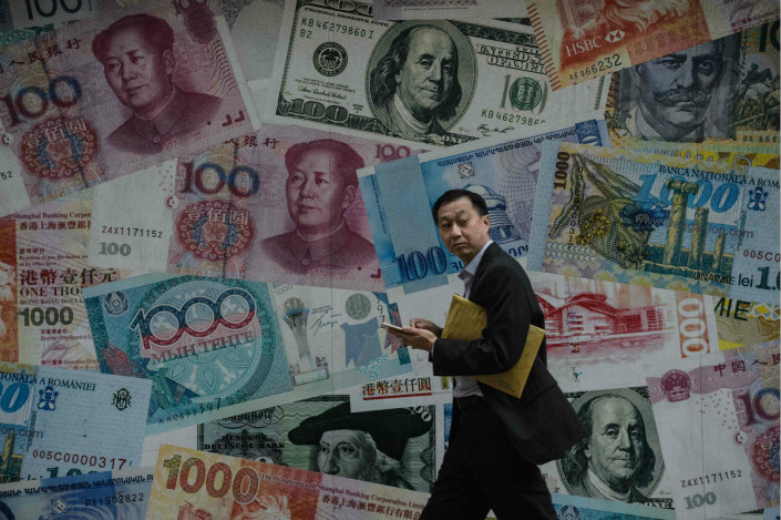 A man walks past a wall emblazoned with representations of different countries' bank notes in Hong Kong on Nov. 9. Photo: VCG