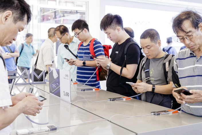 Customers look at smartphones displayed in a Xiaomi store on Hong Kong's Nathan Road on May 7. Photo: VCG