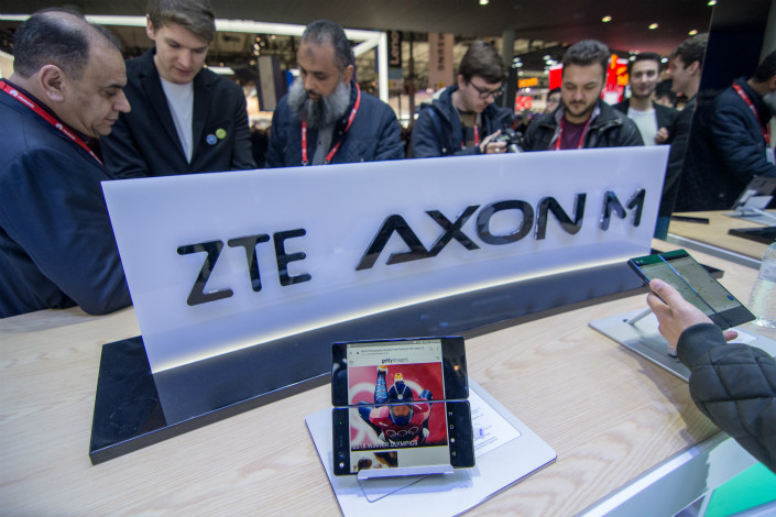 Mobile World Congress 2018 attendees use the ZTE Axon M mobile phone on Feb. 26 in Barcelona, Spain. Photo: VCG