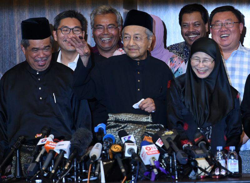 Newly-elected Malaysian Prime Minister and opposition candidate Mahathir Mohamad (Central) waves to the media after a press conference in Kuala Lumpur on May 10, 2018. Photo: VCG