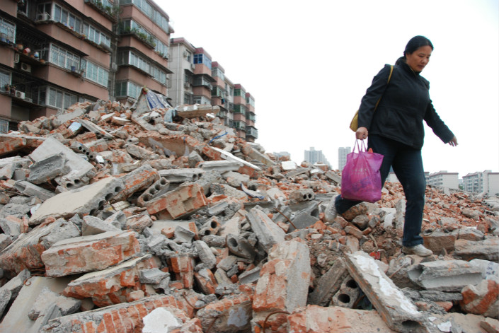 Jia Lingmin stands on the pile of rubble where her home used to be on Oct. 25, 2010. Photo: VCG