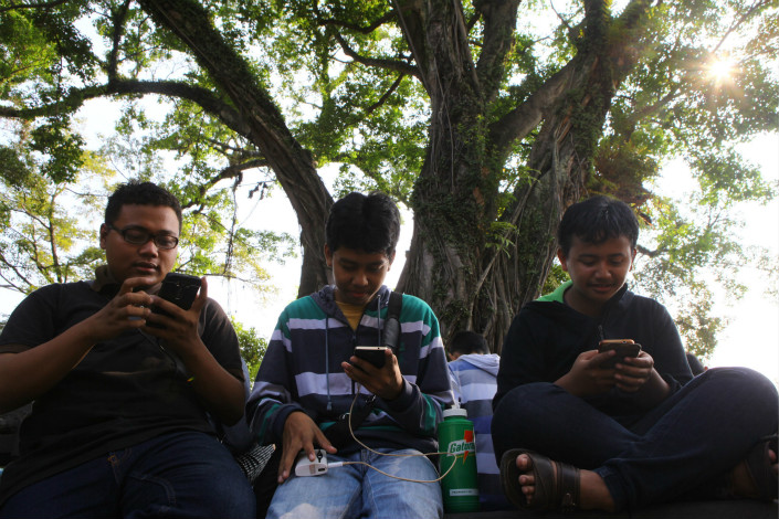 """Pokemon Go"" fans play the game on their cellphones in India in July 2016. Photo: VCG"