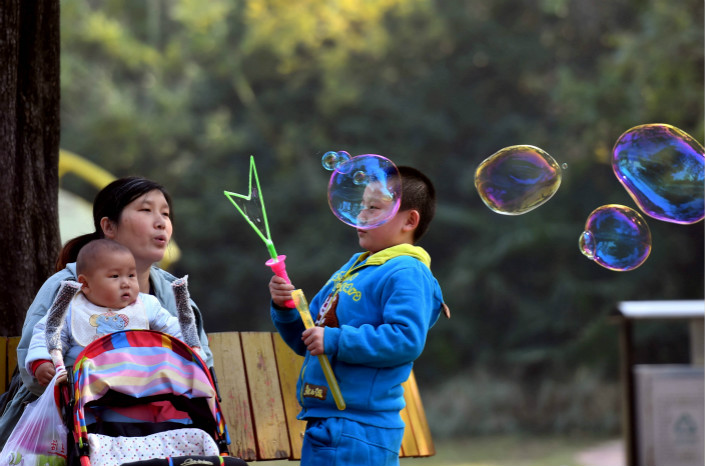 A mother plays with two children at a park in the northern city of Zhengzhou in November 2016. Photo: VCG