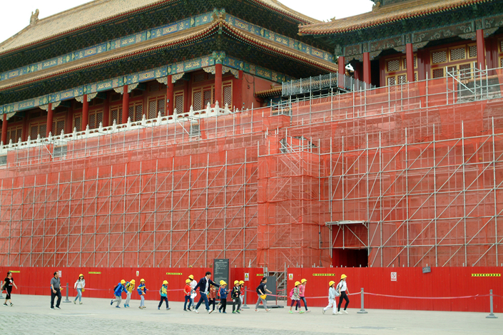 Students attending a traditional-culture program walk past a wall that is being renovated in Beijing's Forbidden City on May 5. Photo: Wu Gang/Caixin