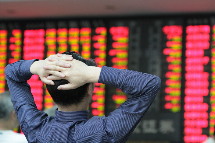 An investor watches a stock listing board at a securities brokerage in the eastern city of Nanjing on Tuesday. Photo: IC